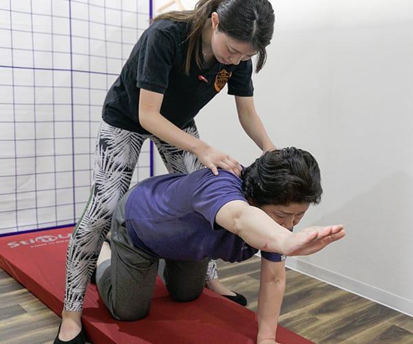 身体のメンテナンスを受けながら運動している写真